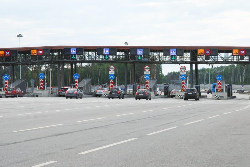 Automobili che aproaching il perno dell'entrata della strada a pedaggio su una strada principale immagine stock