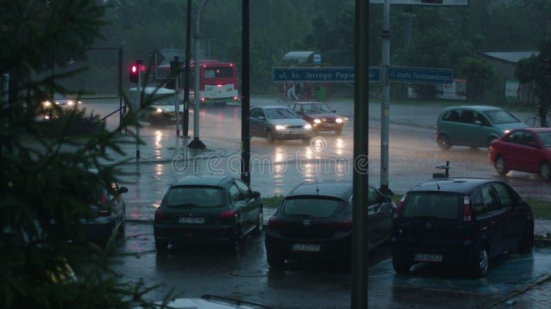 Automobili che corrono con le luci sopra nella pioggia immagini stock