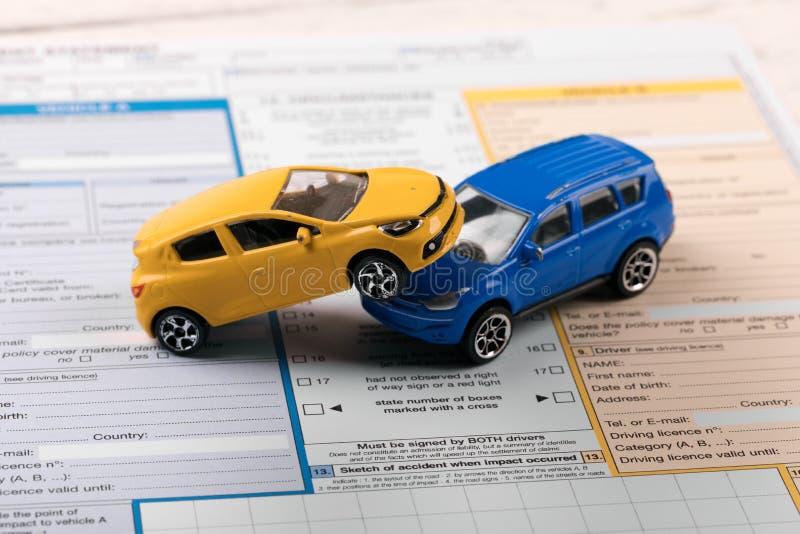 Automobili del giocattolo sulla dichiarazione di incidente immagini stock