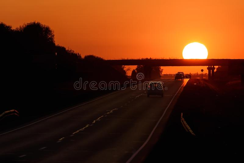 Automobili dell'arancia di tramonto del sole della strada fotografie stock