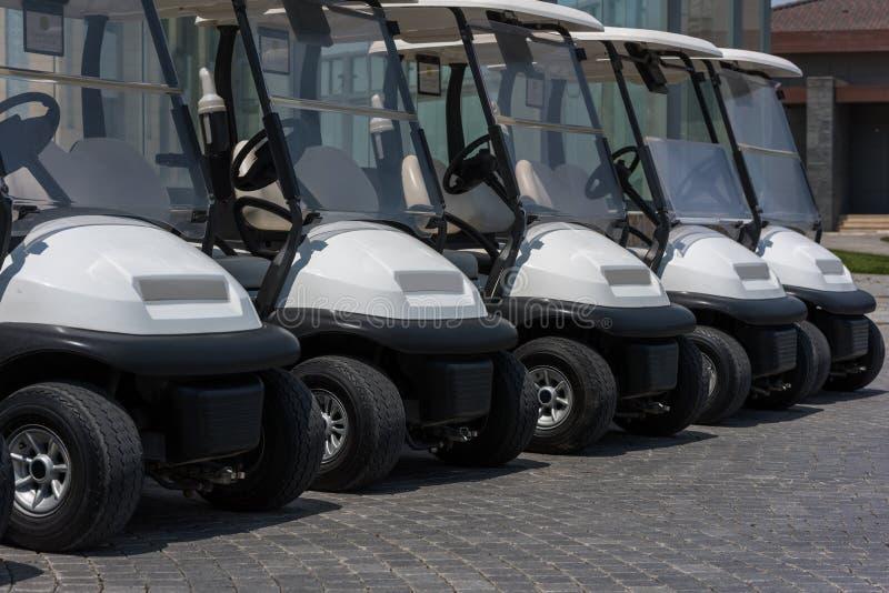 Automobili di golf in una fila fotografia stock