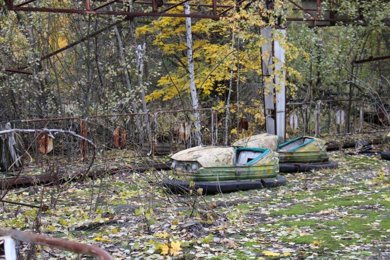 Automobili gialle radioattive del vecchio metallo arrugginito rotto, le automobili elettriche dei bambini, abbandonate fra vegeta immagini stock libere da diritti