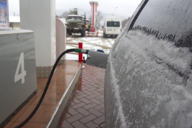 Automobili nella neve ad una stazione di servizio nell'inverno, una pistola nel carro armato di gas, l'immagine di sfondo fotografie stock libere da diritti