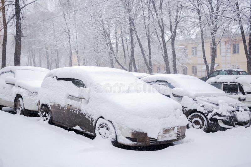 Automobili parcheggiate innevate che stanno in cumulo di neve durante le precipitazioni nevose fotografia stock libera da diritti