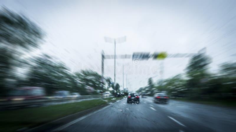Automobili rapide sulla strada principale e sull'effetto confuso immagine stock