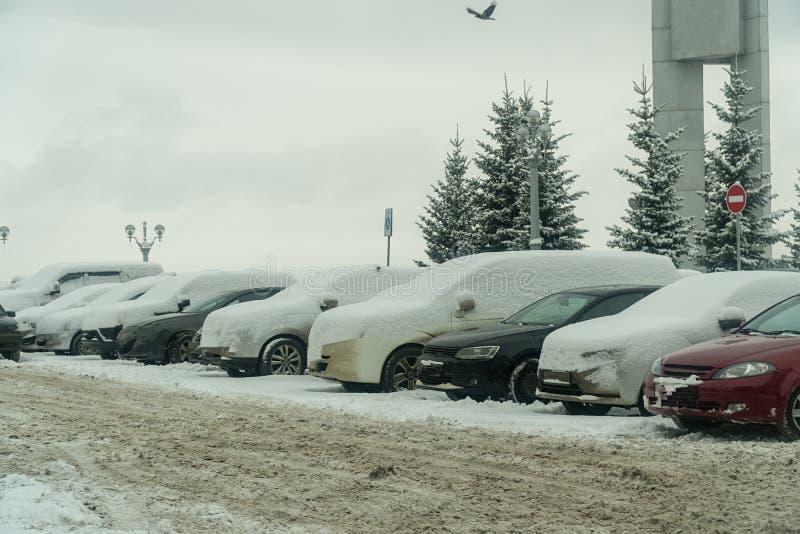 Automobili sotto neve nel parcheggio fotografie stock