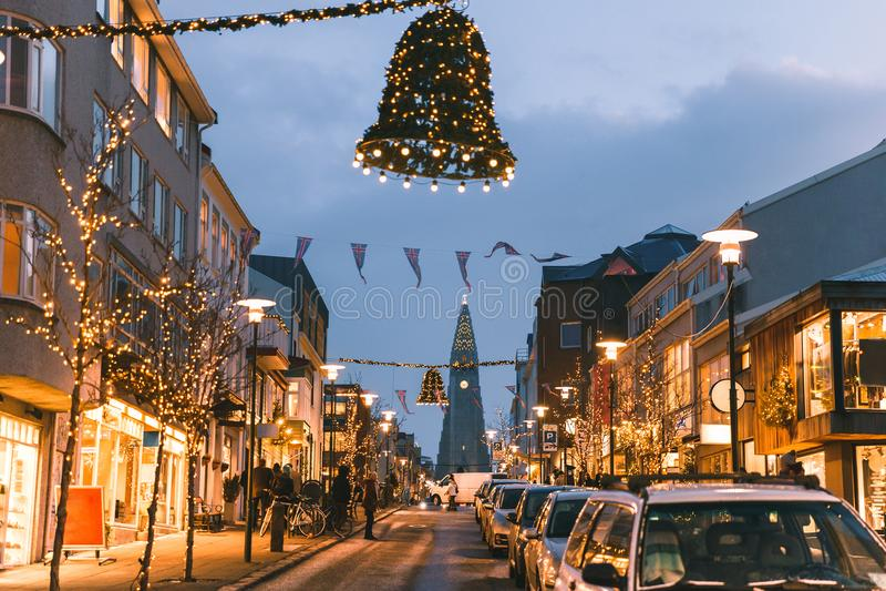 automobili sulla strada e belle costruzioni illuminate sulla via a Reykjavik, Islanda immagine stock libera da diritti