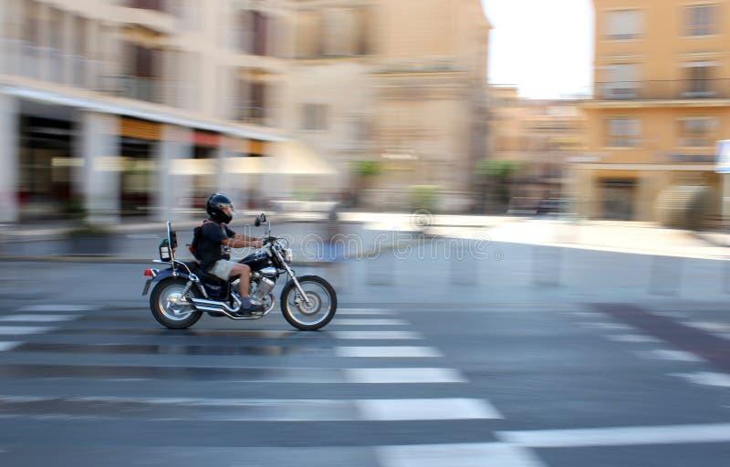 Automobilista che guida velocemente sul suo motociclo e su un paesaggio astratto ai precedenti fotografia stock libera da diritti