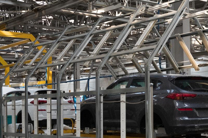 Automotive factory. The body of a modern black car on a lift. Conveyor production line of vehicles. Background for banner or. Automotive factory. Background for stock photo