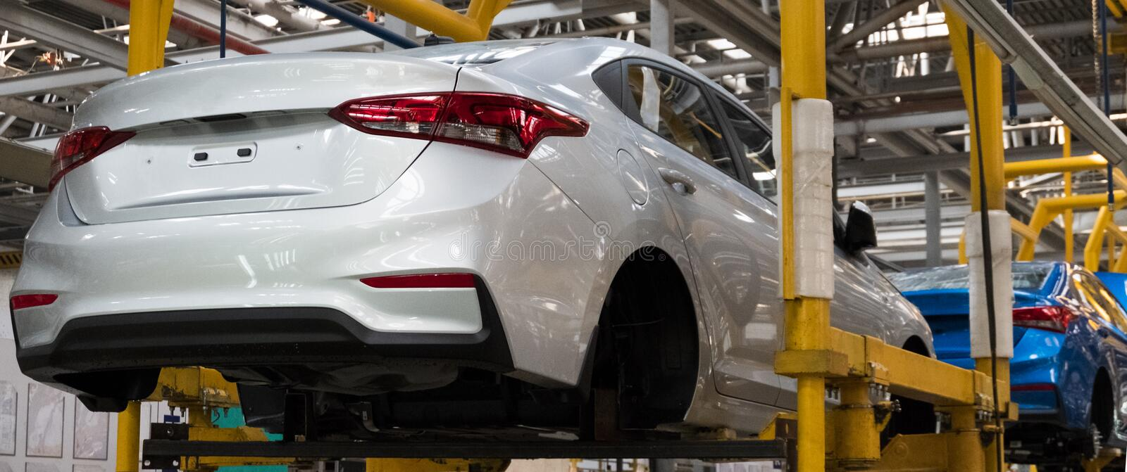 Automotive factory. The body of a modern white car on the lift. Conveyor production line of vehicles. Background for banner or. Automotive factory. The body of a stock photos