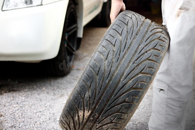 Automotive mechanic in white uniform holding tire for fixing at the repair garage background. Car insurance concept. Automotive mechanic in white uniform royalty free stock images