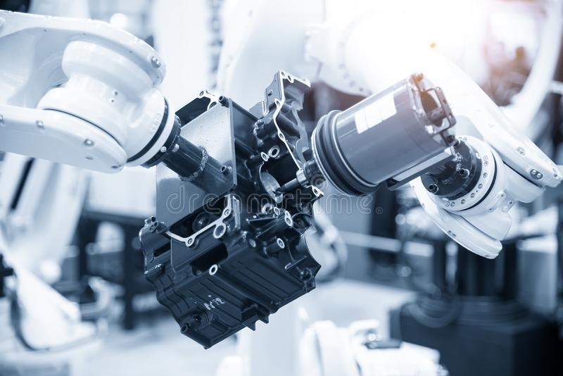 The automotive parts finishing process by milling spindle attach at the robotic arm. The aluminium casting gearbox parts machining process by automatic stock image
