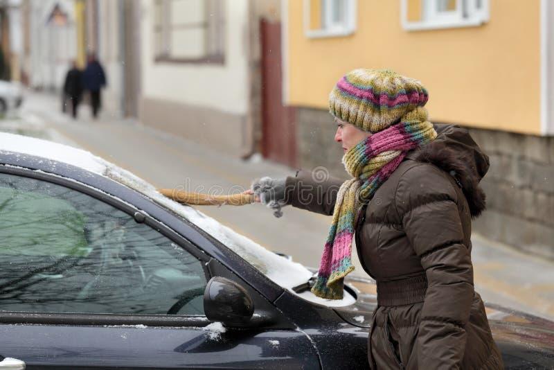 Automotivo, a mulher remove a neve de um carro imagens de stock royalty free