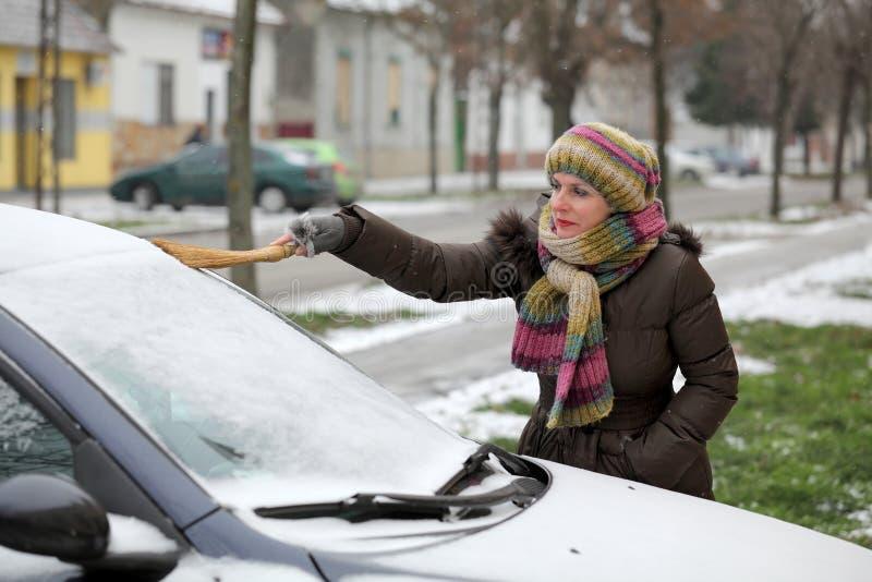 Automotivo, a mulher remove a neve de um carro foto de stock