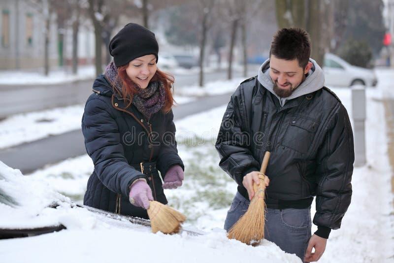 Automotivos, os pares removem a neve de um carro foto de stock royalty free