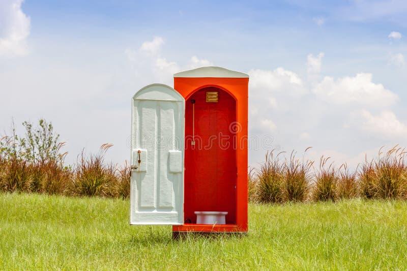 Autonome de la toilette rouge avec le contraste ouvert de porte blanche avec le gree images libres de droits