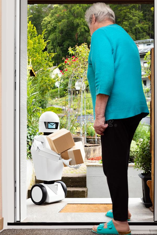 Autonomous ai artificial intelligence robot is delivering parcels or boxes. Senior woman is receiving post from an futuristic robotic delivery service royalty free stock photography