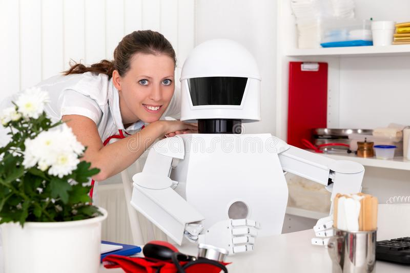 Autonomous medical robot doctor is sitting behind the desktop in. A surgery or office, female doctor or nurse on his side, looking to the viewer royalty free stock photos