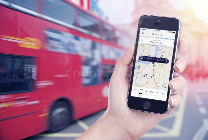 Autoonderzoek door Uber app die op Apple-het iPhonescherm in vrouwelijke hand wordt getoond royalty-vrije stock foto