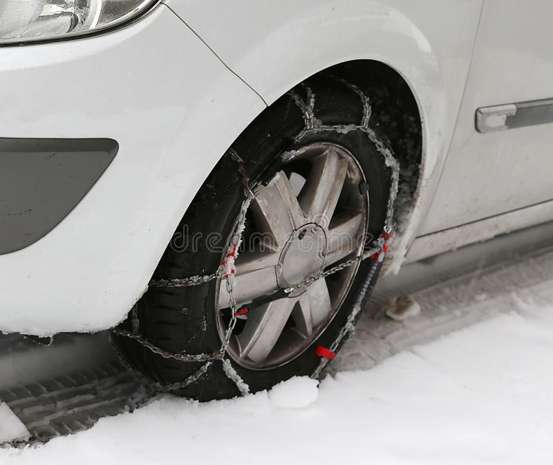 Autoreifen mit Schneeketten im Winter stockbild