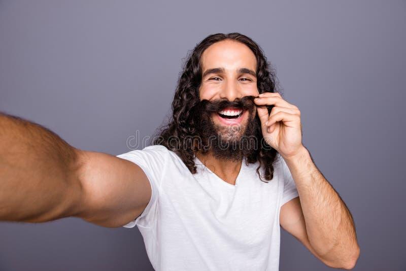 Autoritratto del suo lui tipo dai capelli ondulati pazzo di buon umore allegro attraente governato piacevole che fa baffi falsi c immagini stock