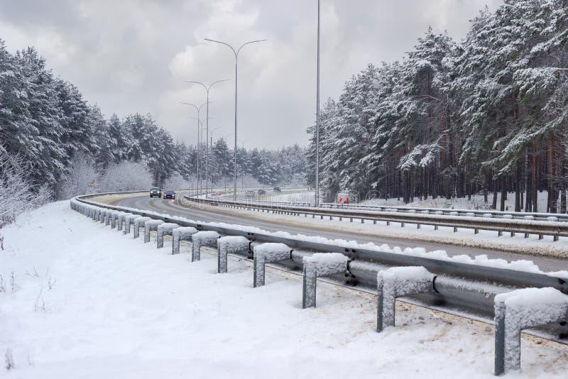 Autoroute avec la forêt des deux côtés après des chutes de neige photos libres de droits