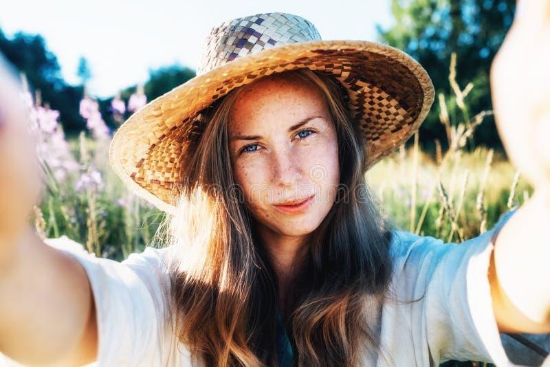 Autorretrato da mulher de sorriso loura nova bonita foto de stock