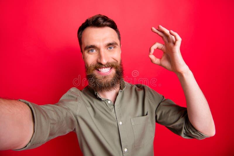 Autorretrato do homem que veste a exibição que cinzenta da camisa você assina está bem a fim o recomendar que algo está satisfeit foto de stock royalty free