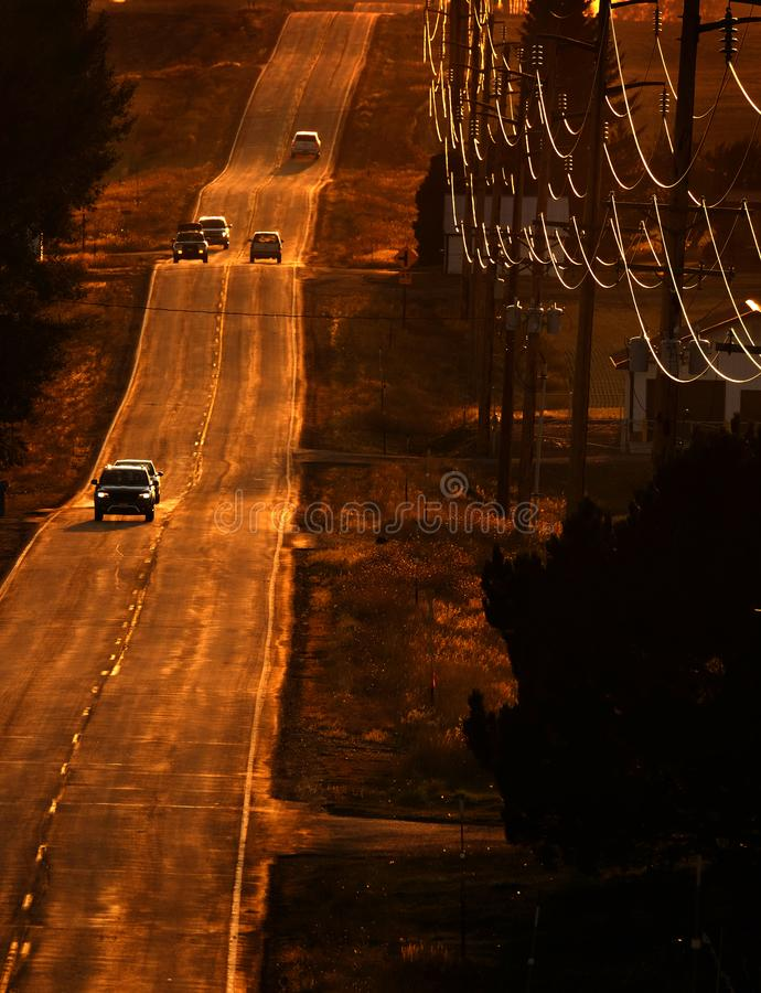 Autos conduciendo por carretera del condado al atardecer o al amanecer imágenes de archivo libres de regalías