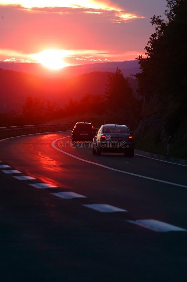 Autos im Sonnenuntergang stockbilder