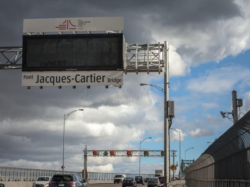 Autos u. LKW-Verkehr auf der Autobahn von Jacques Cartier-Brücke mit seinem Logo, in der Richtung nach Montreal stockfotografie