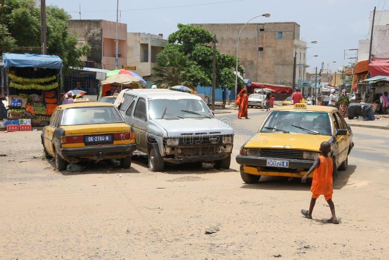 Autos und Kind in einem Quadrat in Dakar, Senegal lizenzfreie stockfotos