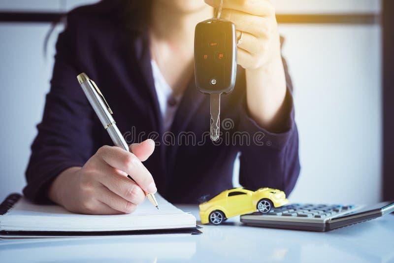 Autoschlüssel an Hand mit Autohaus und Miete, Autofinanzkonzept lizenzfreies stockbild