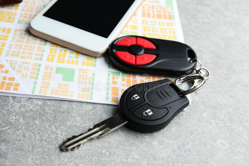 Autoschlüssel, -telefon und -karte auf Tabelle stockbilder