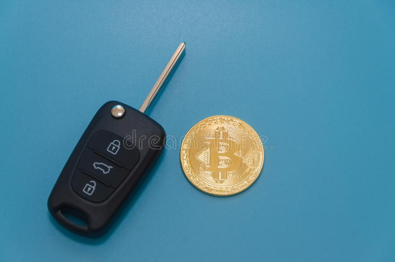 Autoschlüssel und cryptocurrency Gold-bitcoin, auf blauem Hintergrund stockfotografie