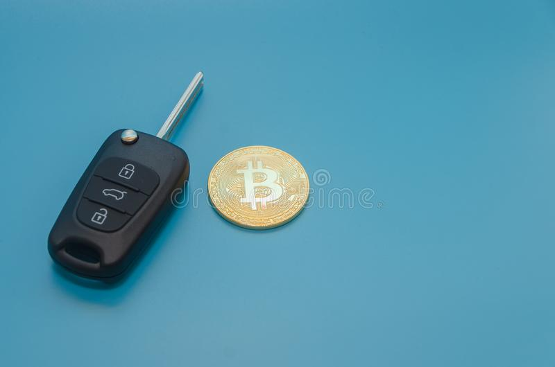 Autoschlüssel und cryptocurrency Gold-bitcoin, auf blauem Hintergrund lizenzfreie stockfotografie