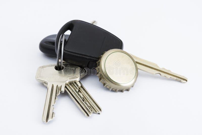 Autoschlüssel und Flaschenkapsel im Abschluss oben lizenzfreies stockfoto