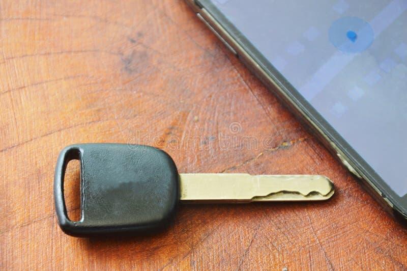 Autoschlüssel und intelligentes Telefon öffneten Karte auf Tabelle lizenzfreies stockfoto