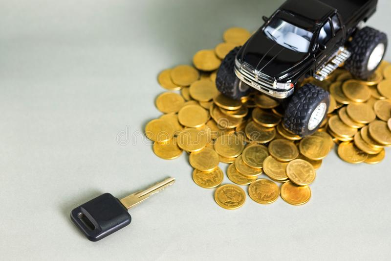 Autoschlüsselminiaturautokleintransporter auf Stapeln Münzen auf grauem Ba lizenzfreies stockbild