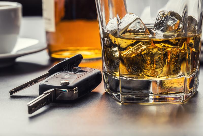 Autosleutels en glas van alcohol op lijst royalty-vrije stock afbeeldingen