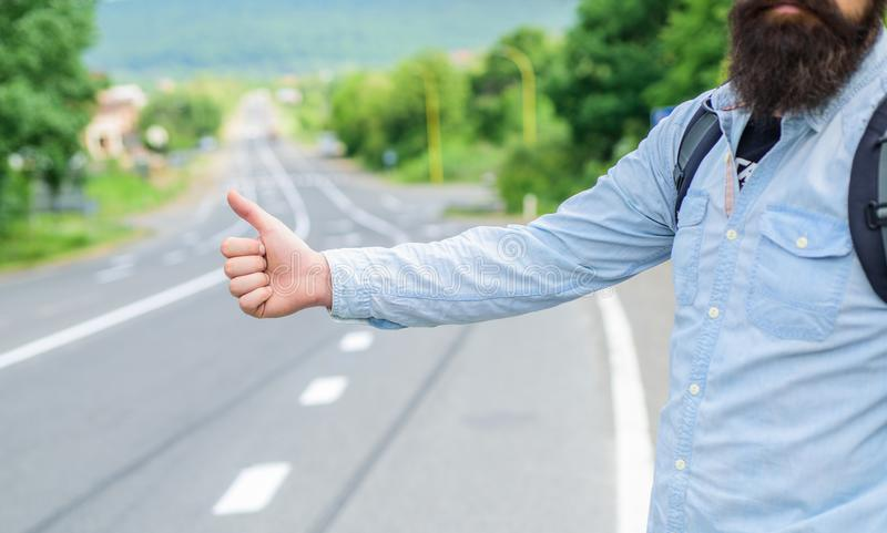 Autostop travel. Pick me up. Thumb up gesture try stop car road background. Hand gesture hitchhiking. Make sure you know royalty free stock image