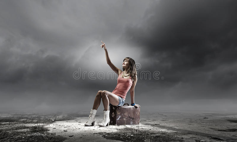 Autostop travel. Young pretty girl traveler sitting on suitcase aside of road stock images