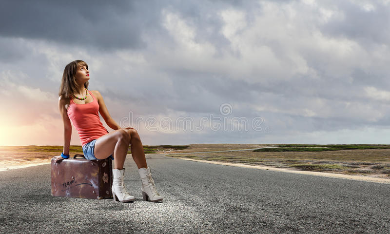 Autostop travel. Young pretty girl traveler sitting on suitcase aside of road royalty free stock photography