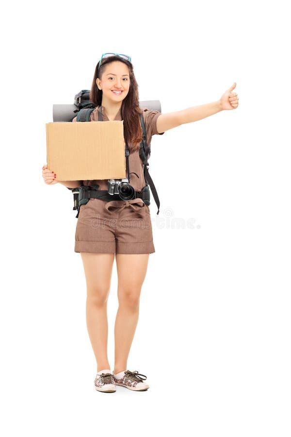 Autostopista femenino que lleva a cabo una muestra en blanco del cartón fotos de archivo