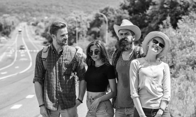Autostopistas de los amigos que buscan día soleado del transporte Viajeros de los amigos de la compañía que hacen autostop en la  fotografía de archivo