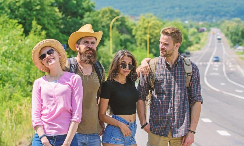 Autostopistas de los amigos que buscan día soleado del transporte Viajeros de los amigos de la compañía que hacen autostop en la  fotografía de archivo libre de regalías