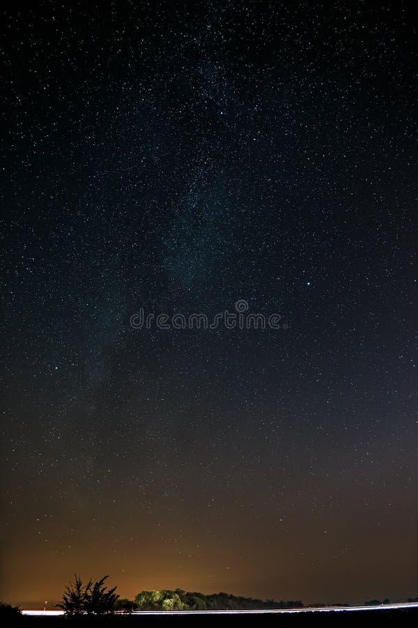 Autostrada na tle jaskrawe gwiazdy nocne niebo i fotografia royalty free
