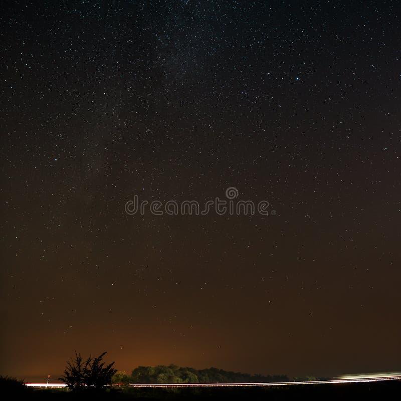 Autostrada na tle jaskrawe gwiazdy nocne niebo i zdjęcie royalty free