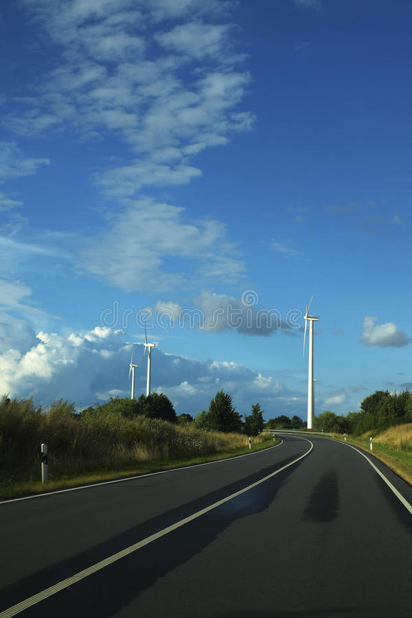 Autostrada prowadzi trzy wiatrowego koła przeciw niebieskiemu niebu z w zdjęcie royalty free