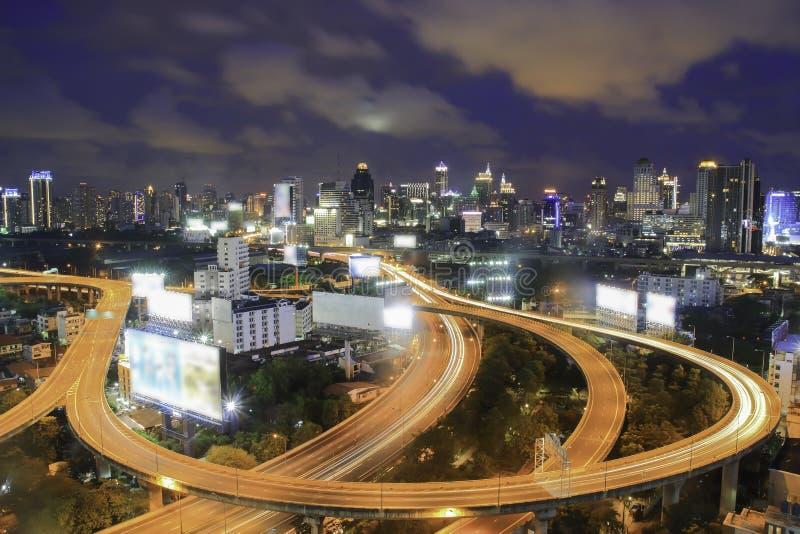 Autostrada w nocy z samochodami zaświeca w nowożytnym mieście zdjęcie royalty free